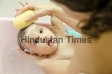 Baby,Having,A,Bath,,Mother,Cleaning,With,Sponge,His,Little