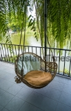 Comfortable,Hanging,Rattan,Swing,Chair,With,Fabric,Cushions,On,Garden