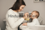 Mom,Feeding,Her,Baby,Girl,With,A,Spoon.,Mother,Giving