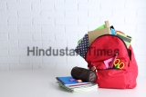 Backpack,With,School,Supplies,On,Wooden,Table,,On,Wall,Background